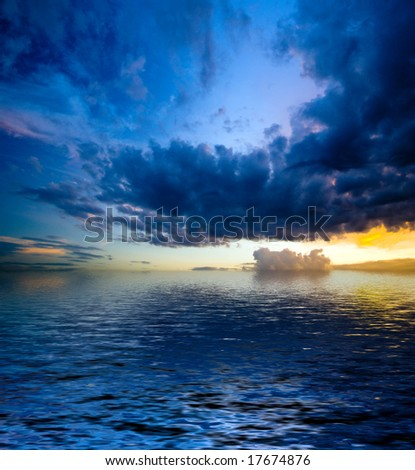 colorful dramatic landscape with water and cloudy sky at sunset