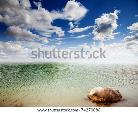 colorful dramatic landscape with water,stone and cloudy sky