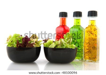 Colorful dressing with herbs in glass bottles with salad