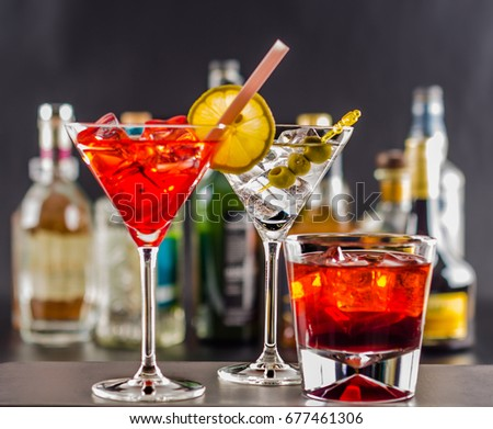 Colorful drink on the background of bottles in original shapes, cocktail drink with ice cubes, party night #677461306