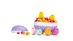 Colorful Easter chicks taking an Easter egg filled with Easter egg candies and runs away with it. Easter concept on pure white background.