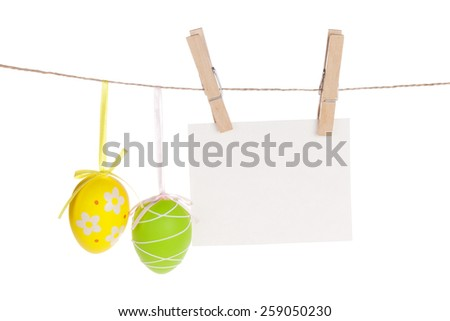 Colorful easter eggs and blank photo frame hanging on rope. Isolated on white background