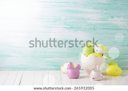 Colorful easter eggs and hens  in ray of light on mint wooden background. Easter background.Toned image.Selective focus.