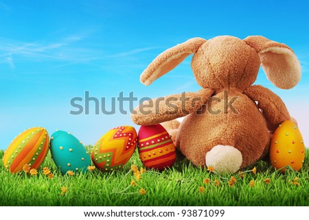 Colorful easter eggs and rabbit on green grass