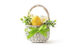 colorful easter eggs and spring flowers in basket isolated on white background