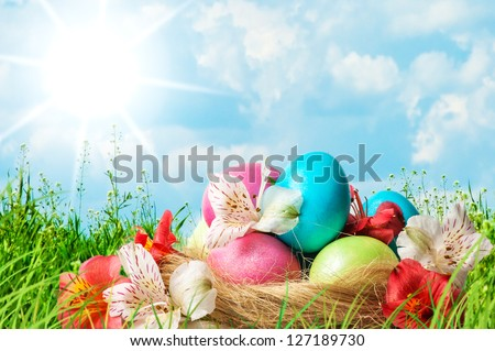 Colorful Easter eggs decorated with flowers in basket in the grass on blue sky background