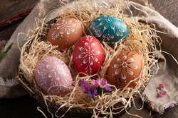 Colorful Easter eggs decorated with wax in a basket