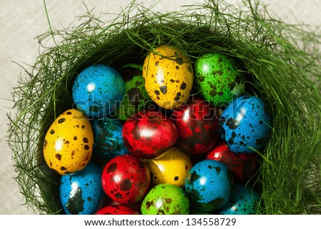 Colorful Easter eggs in a bowl decorated with a nest