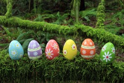 Colorful Easter eggs in a mossy forest.