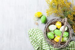 Colorful easter eggs in basket and mimosa flowers on wooden table.  Top view with copy space