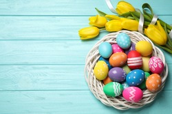 Colorful Easter eggs in decorative nest and tulip flowers on light blue wooden background, flat lay. Space for text
