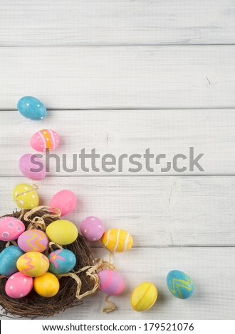 Colorful Easter Eggs in Nest from Top Side View on White or Gray Rustic Wood Background with room or space for copy, text, words  #179521076