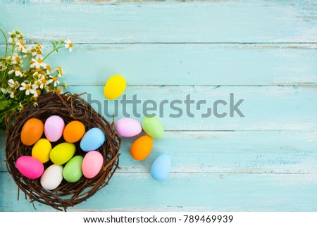Colorful Easter eggs in nest with flower on rustic wooden planks background in blue paint. Holiday in spring season. vintage color tone style. top view composition.