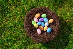 colorful Easter eggs in the nest on fresh green green grass top view, Spring, April, Easter, Holliday concept background copy space cheerful