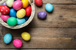 Colorful Easter eggs in wicker basket on wooden table, flat lay. Space for text