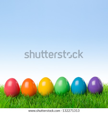 Colorful easter eggs on a fresh meadow, isolated over a bright spring sky.