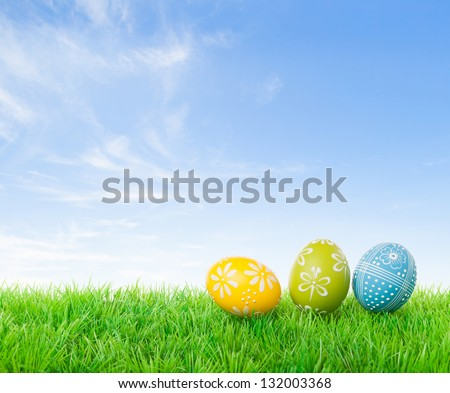Colorful easter eggs on meadow over bright spring sky.