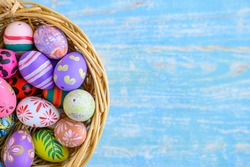 Colorful easter eggs placed in a basket on a blue scratch-like w