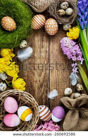 Colorful easter eggs with feathers on old wooden table #260692586