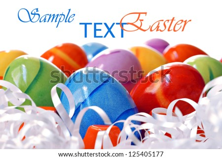 Colorful Easter eggs with ribbon on white background with copy space.  Macro with shallow dof.  Selective focus on blue egg.