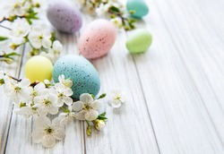 Colorful Easter eggs with spring blossom flowers over wooden background. Colored Egg Holiday border.