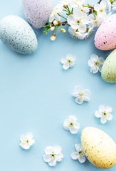 Colorful Easter eggs with spring blossom flowersover blue background. Colored Egg Holiday border.