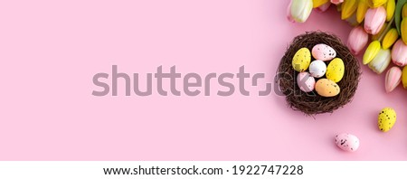 Colorful easter quail eggs in nest and tulips on pink background with . Flat lay. Spring composition. Happy easter greeting card. Copy space Foto d'archivio ©