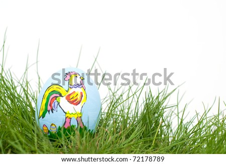 Colorful Easter Rooster hand painted on an egg shell, in green spring grass with copy space