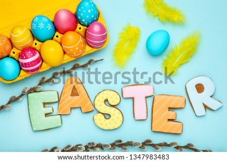 Colorful eggs with word Easter and willow branches on blue background