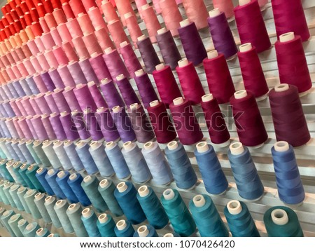 Colorful embroidery thread spool using in garment industry, row of multicolored yarn rolls, sewing material selling in the market