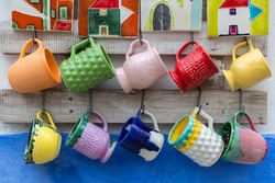 Colorful Empty Cups Hanging on a Wall