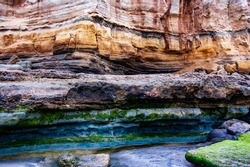 Colorful erosion on cliff rocks from salt water, off the coast on a beach in San Diego