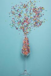 colorful explotion from champagne glass with blue background. Simple concept
