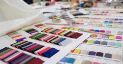 Colorful Fabric and Thread catalog on Seamstress or dressmaker work table background.