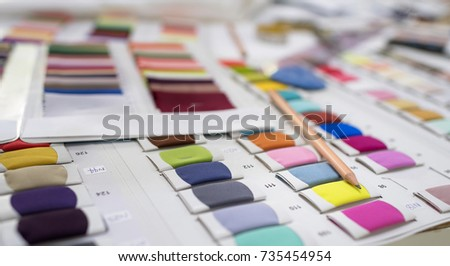 Colorful Fabric and Thread catalog on Seamstress or dressmaker work table background. Setup studio shooting. #735454954