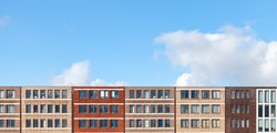 Colorful facades of living houses in a row under blue cloudy sky, Amsterdam, Netherlands