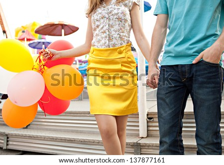 Colorful faceless view of a young couple visiting an amusement park arcade, holding balloons next to an attraction ride.