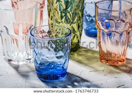 Colorful faceted and geometric drink glass, group of empty green, red, blue and transparent drinkware for beverage on stone concrete background, angle view