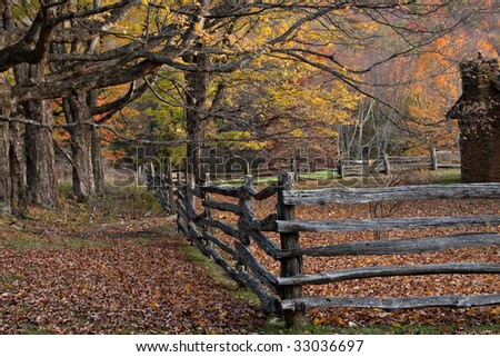 Colorful Fall trees and split rail fence in Virginia mountains.  The chimney of a log cabin is shown.
