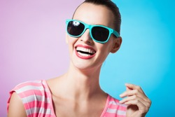 Colorful fashion portrait of young woman smiling and wearing sunglasses.