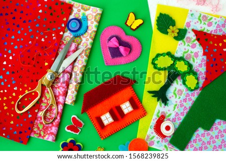 Colorful felt and crafts. Crafts from felt on a green background. Felt for needlework and hobby. Butterfly, house, snail, tree made of felt.