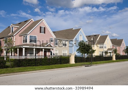 Colorful fenced in row houses with blue sky