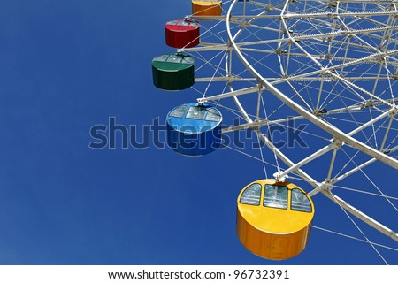Colorful ferris wheel cab suspended high above ground against a clear blue sky. #96732391