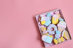 Colorful festive gingerbread cookies of different shapes covered with glaze on pink background copy space.
