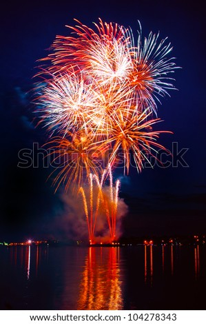 Colorful firework in a night sky, reflection in water