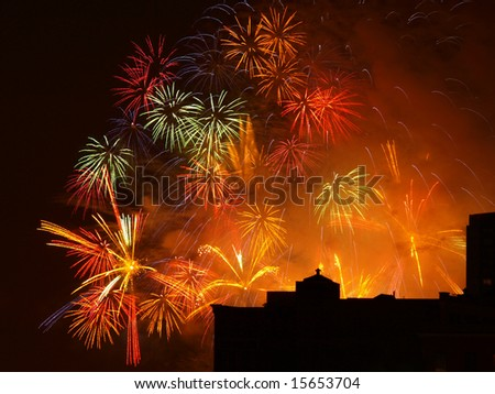 Colorful Fireworks burst display with building silhouette