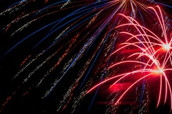 Colorful fireworks explode from the edges of the frame in a fireworks show celebrating July 4th Independence Day.