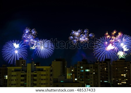 Colorful fireworks over a night sky in the city.