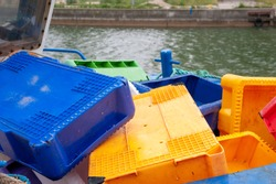Colorful fish crates on the board of fishing boat