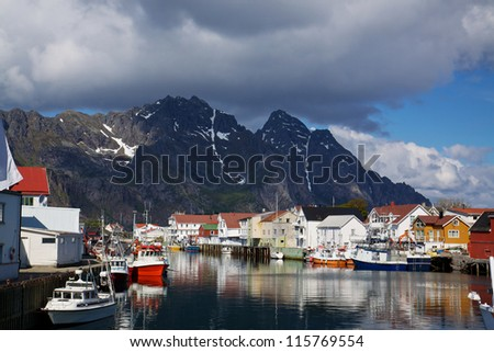 Colorful fishing harbor on Lofoten Islands in Norway with mountains towering in the background